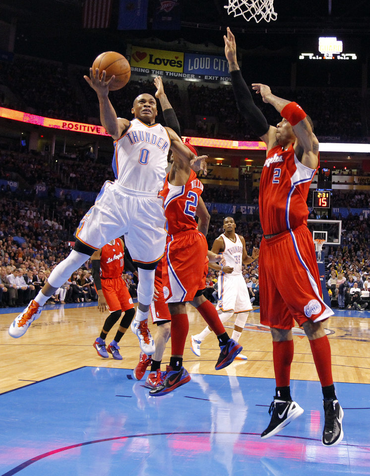 Photo - Oklahoma City Thunder point guard Russell Westbrook (0) drives to the basket past Los Angeles Clippers point guard Mo Williams (25) and Los Angeles Clippers power forward Kenyon Martin (2) during the NBA basketball game between the Oklahoma City Thunder and the Los Angeles Clippers at Chesapeake Energy Arena on Wednesday, March 21, 2012 in Oklahoma City, Okla.  Photo by Chris Landsberger, The Oklahoman