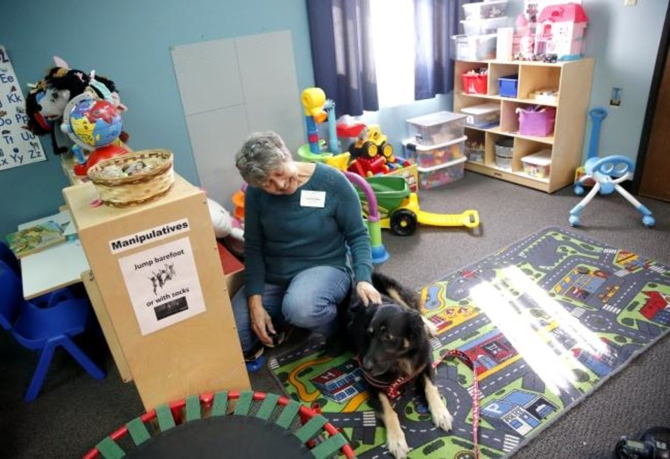 Photo -  Carol Gardner pets therapy dog Charlie in the daycare room at Palomar in Oklahoma City. [Sarah Phipps/The Oklahoman]