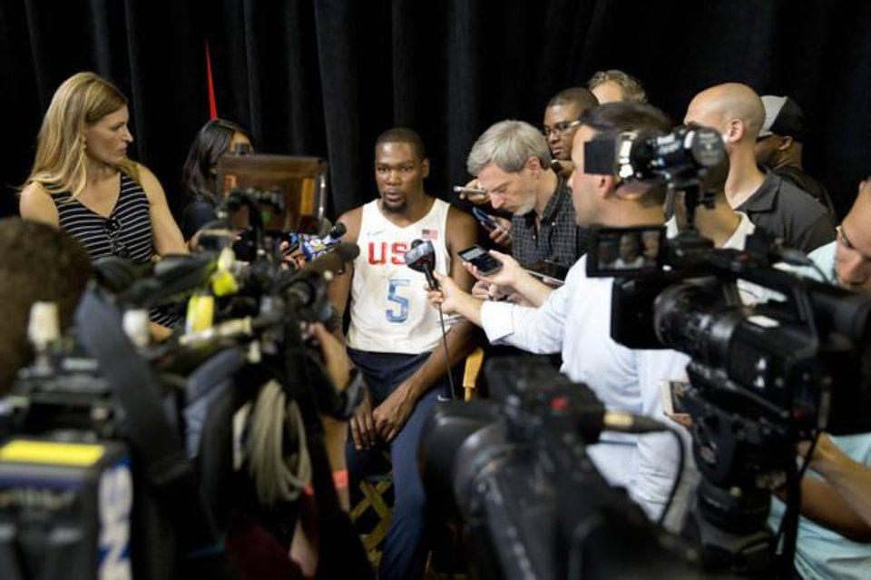 Photo - Oklahoma City star Kevin Durant, shown here in his Team USA uniform, is interviewed by reporters. Many questions surround his free agency and who he will sign with this summer. (AP Photo)