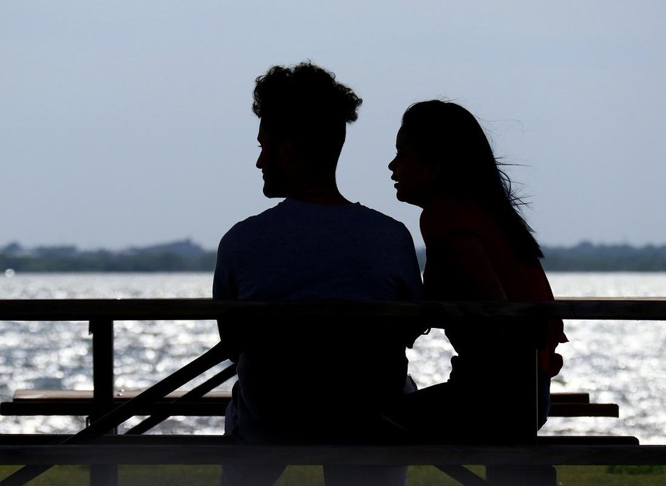 Photo - A couple sit in the shade at a picnic table and watch sail surfers enjoy the windy conditions at Lake Hefner Monday, April 27, 2020. [Doug Hoke/The Oklahoman]