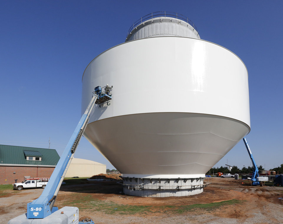 Photo -  Painters begin their work on the design of the newest water tower Friday at Broadway and Coffee Creek in Edmond. [Photo by Paul Hellstern, The Oklahoman]