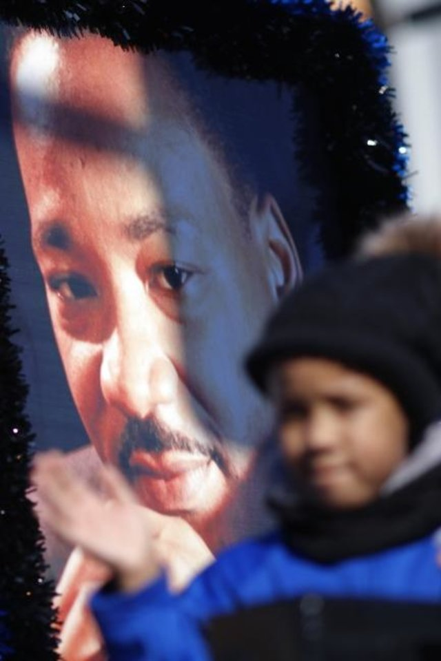 Photo -  A young girl waves to the crowd from a float with a poster of Martin Luther King Jr. at the 2020 Martin Luther King Holiday Parade in Oklahoma City. The 2021 holiday parade and other activities will be virtual. [Doug Hoke/The Oklahoman]
