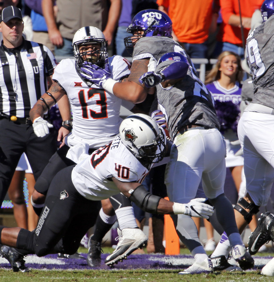 Photo -  TCU's Kyle Hicks is stopped after taking a direct snap near the goal line by OSU's Devante Averette (40) during Saturday's game in Fort Worth, Texas. [PHOTO BY STEVE SISNEY, THE OKLAHOMAN]