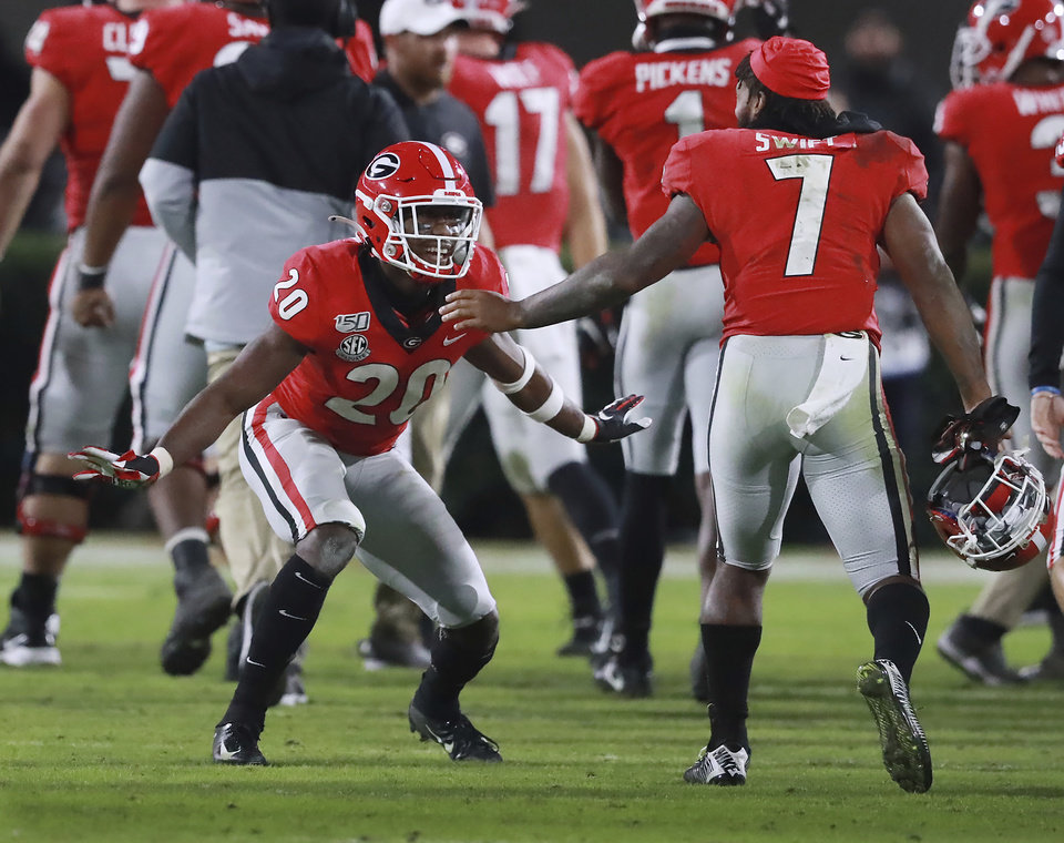Photo - Georgia defensive back J.R. Reed, left, celebrates after stopping Missouri on fourth down with tailback D'Andre Swift (7) to take over on downs in the final minutes of the fourth quarter and preserve a shutout in an NCAA college football game Saturday, Nov. 9, 2019, in Athens, Ga. (Curtis Compton/Atlanta Journal Constitution via AP)
