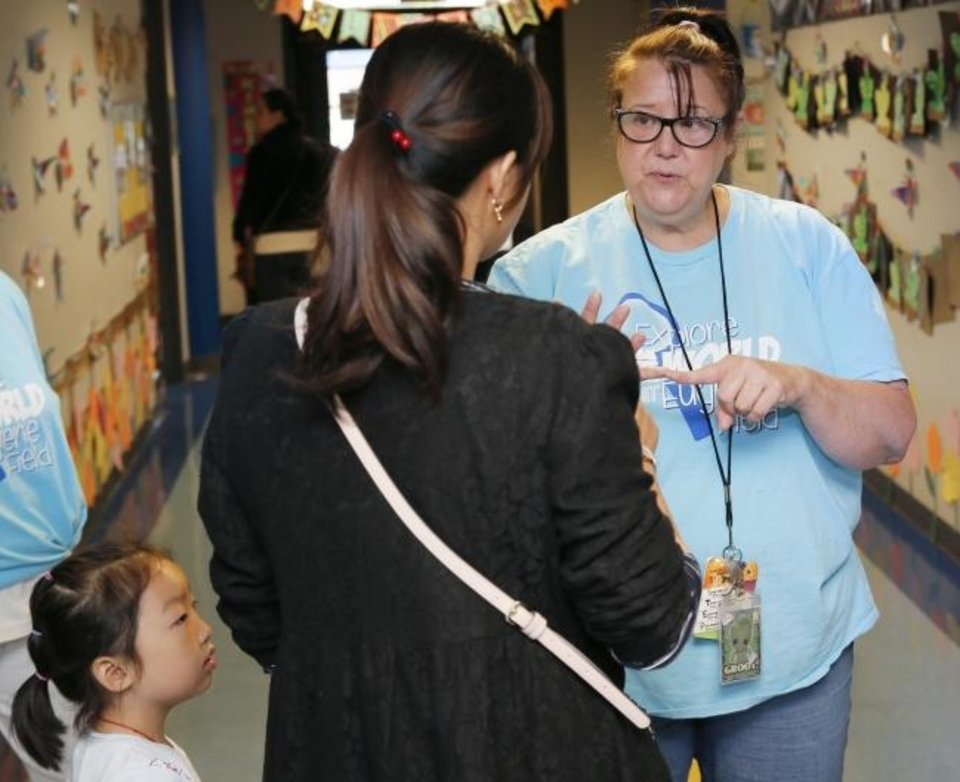 Photo -  Special education teacher Karrie Terrell, right, talks to parent Angela Chen with her daughter Coco Chen, 6, next to her, during a tour Saturday at Eugene Field Elementary. [Nate Billings/The Oklahoman]