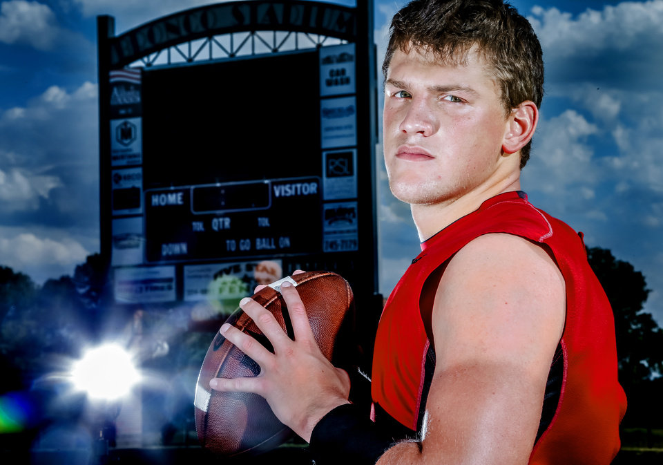 Photo - Mustang High School quarterback Chandler Garrett poses for a photo at the school's football stadium in Mustang, Okla. on Wednesday, Oct. 1, 2014.  Photo by Chris Landsberger, The Oklahoman