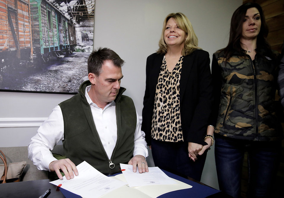 Photo - Oklahoma Gov. Kevin Stitt(left) signs a pardon for Rhonda Bear as she holds hands with her daughter Sara Williams  at She Brews Coffee House in Claremore Thursday, Nov. 7, 2019. MIKE SIMONS/Tulsa World