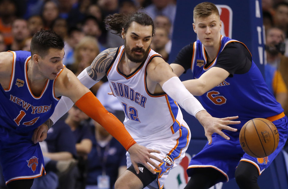 Photo - Oklahoma City's Steven Adams (12) goes for the ball between New York's Willy Hernangomez (14) and Kristaps Porzingis (6) during an NBA basketball game between the Oklahoma City Thunder and the New York Knicks at Chesapeake Energy Arena in Oklahoma City, Wednesday, Feb. 15, 2017. Photo by Bryan Terry, The Oklahoman