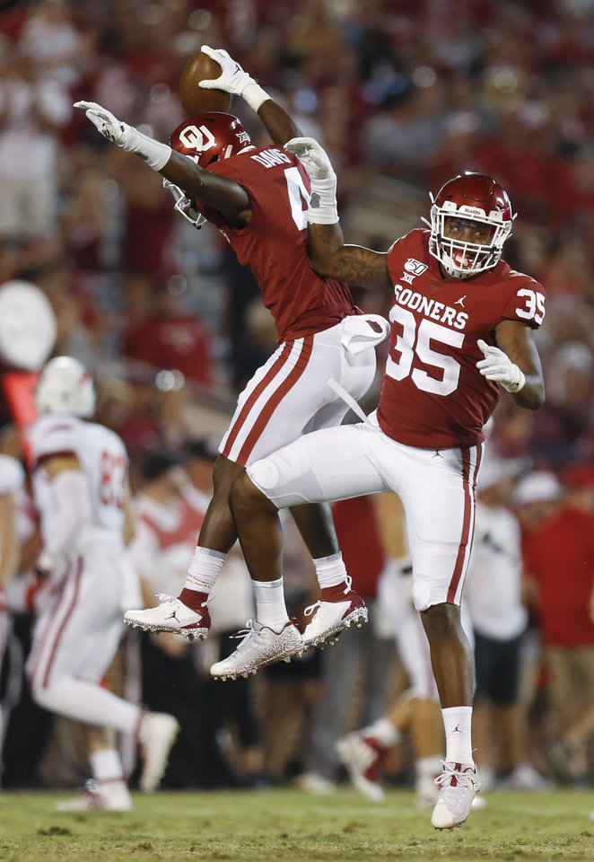 Photo - Oklahoma's Jaden Davis (4) and Nik Bonitto (35) celebrate after an interception by Davis in the fourth quarter during a college football game between the Oklahoma Sooners (OU) and South Dakota Coyotes at Gaylord Family - Oklahoma Memorial Stadium in Norman, Okla., Saturday, Sept. 7, 2019. [Nate Billings/The Oklahoman]