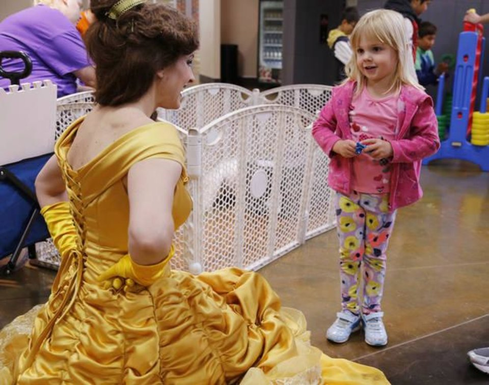 Photo -  Madalynn Burns, 4, talks to Belle, played by Kristie Patton, during Healthy Kids Day at the J.L. Mitch Park YMCA. [PHOTO BY PAUL HELLSTERN, THE OKLAHOMAN]