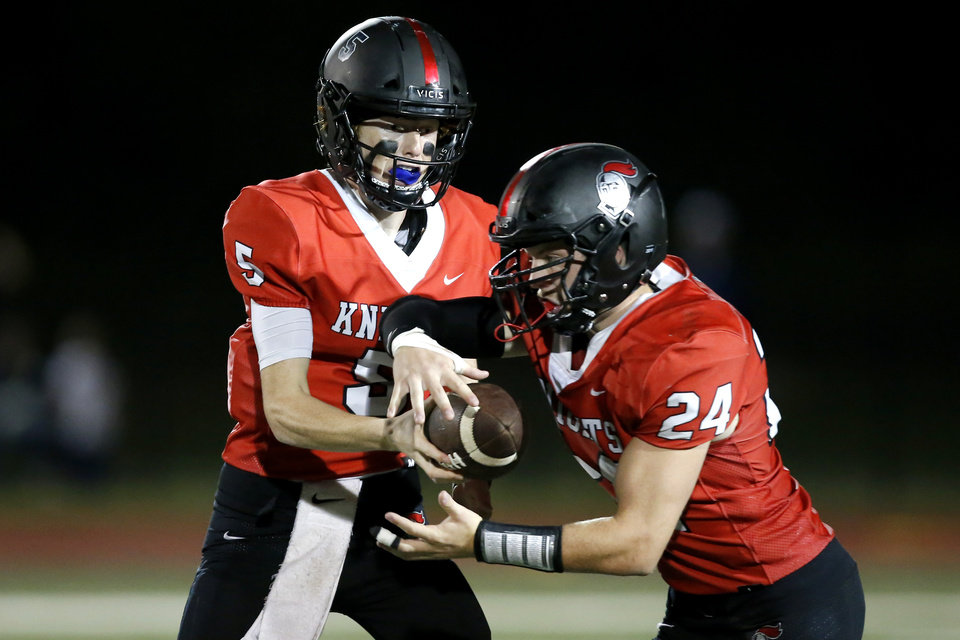 Photo - Mason Snyder of Crossings hands of to Jacob Snyder during a high school football game between Crossings Christian and Minco in Oklahoma City, Friday, Sept. 13, 2019. [Bryan Terry/The Oklahoman]