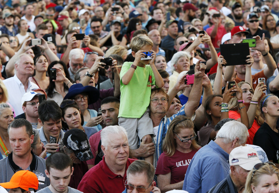 Photo - People in the back of the crowd listen and take pictures during an appearance by Republican presidential candidate Donald Trump during the Oklahoma State Fair at State Fair Park in Oklahoma City, Friday, Sept. 25, 2015. Photo by Nate Billings, The Oklahoman