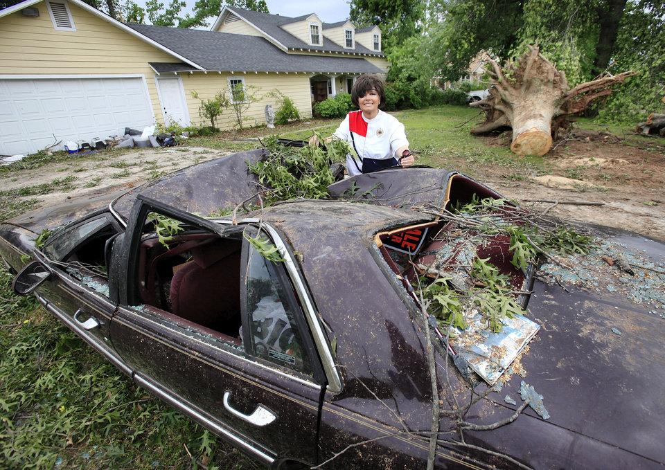 Photo - Ronnye Perry-Sharpe stands behind her crushed 1995 Buick in the driveway of her Tecumseh home Wednesday, May 12, 2010. Perry-Sharpe said she had sold the car last Sunday, the day before a tornado swept through her neighborhood, toppling a 100 year-old oak tree in her front  yard.  The tree fell on the car, smashing it. Perry-Sharpe and her mother were in the house  during the storm. They were not injured.    Photo by Jim Beckel, The Oklahoman