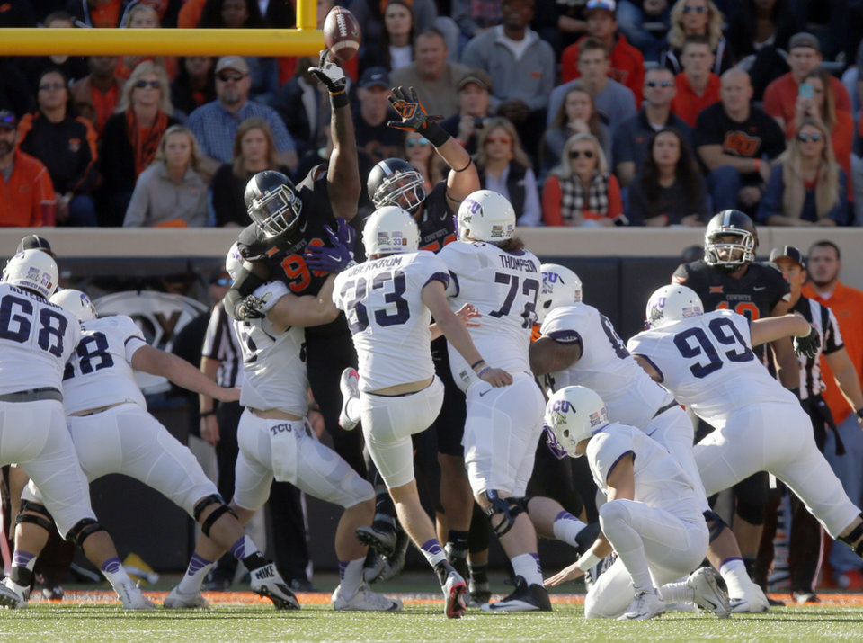 Photo - Oklahoma State's Vincent Taylor (96) blocks the extra point kick of TCU's Jaden Oberkrom (33) during the college football game between the Oklahoma State Cowboys (OSU) and TCU Horned Frogs at Boone Pickens Stadium in Stillwater, Okla., Saturday, Nov. 7, 2015. Photo by Sarah Phipps, The Oklahoman
