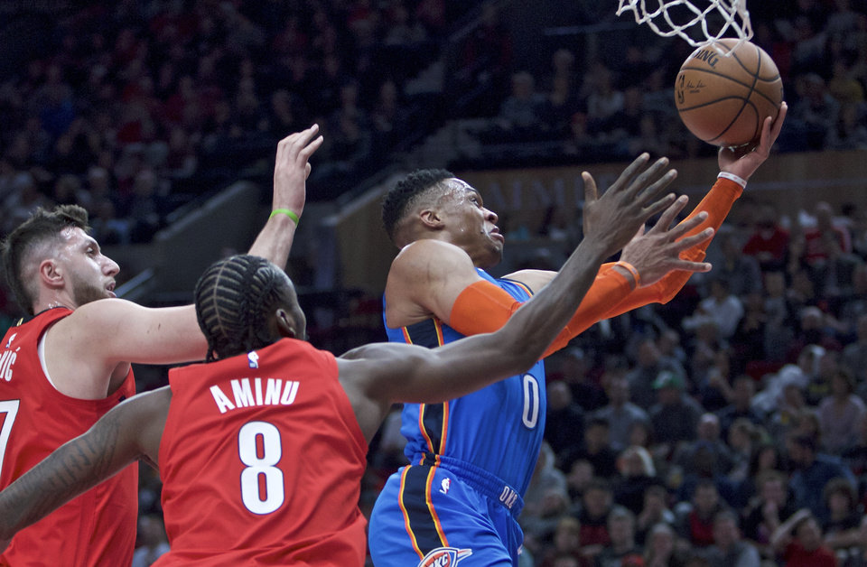 Photo - Oklahoma City Thunder guard Russell Westbrook, right, shoots next to Portland Trail Blazers forward Al-Farouq Aminu, center, and center Jusuf Nurkic during the first half of an NBA basketball game in Portland, Ore., Friday, Jan. 4, 2019. (AP Photo/Craig Mitchelldyer)