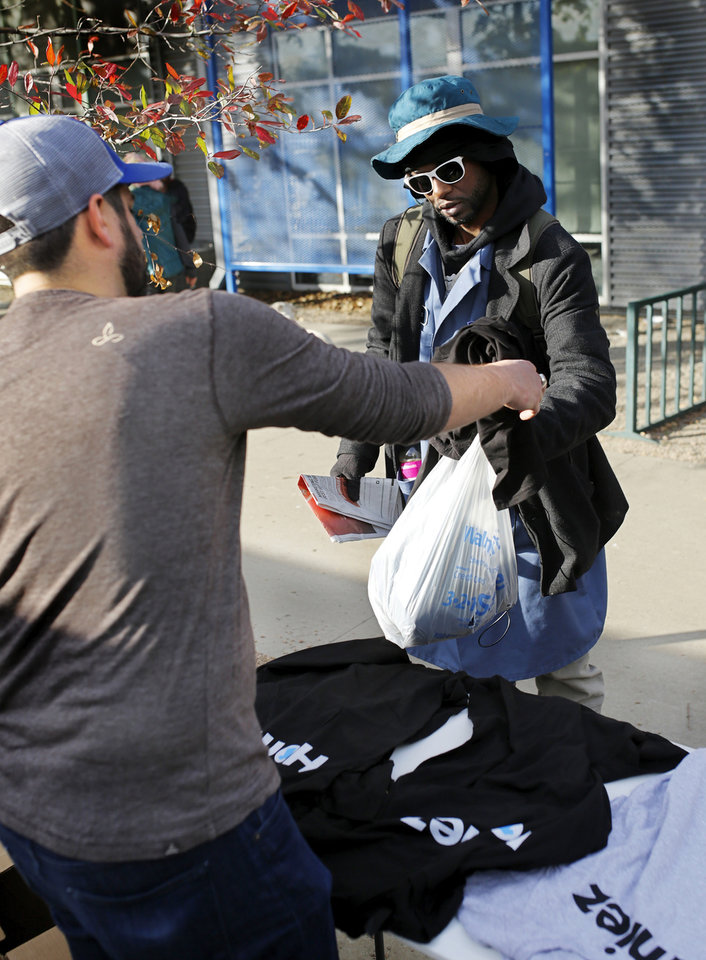 Photo -  Jake Foster hands out free shirts at the Homeless Alliance's WestTown Resource Center. [Photo by Jim Beckel, The Oklahoman]