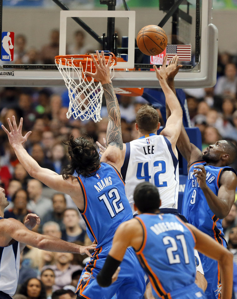 Photo - Dallas Mavericks' David Lee (42) gets by Oklahoma City Thunder's Steven Adams (12) of New Zealand, Andre Roberson (21), and Serge Ibaka (9) to sink a basket in the first half of an NBA basketball game, Wednesday, Feb. 24, 2016, in Dallas. The basket was Lee's first as a Maverick. (AP Photo/Tony Gutierrez)
