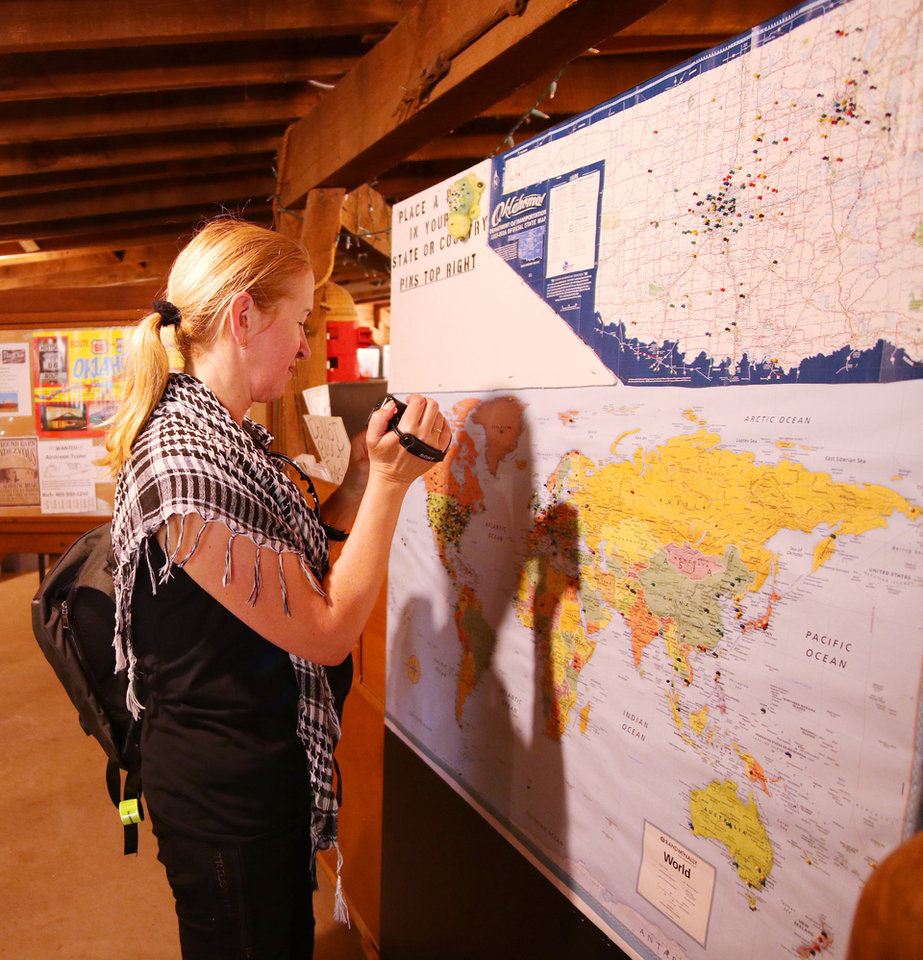 Photo -  Jarka Vojikova, from the Czech Republic, videos the pin map at the Round Barn on Route 66. [Photo by Doug Hoke, The Oklahoman]