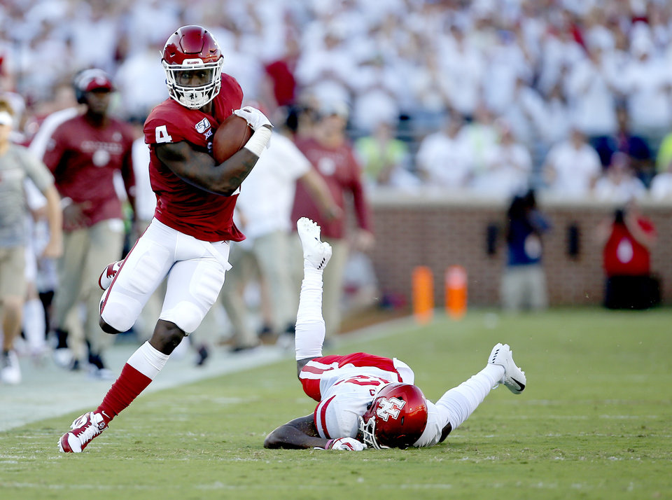 Photo - Oklahoma's Trey Sermon (4) runs after a stiff arm on Houston's Gervarrius Owens (32) in the first quarter aduring a college football game between the University of Oklahoma Sooners (OU) and the Houston Cougars at Gaylord Family-Oklahoma Memorial Stadium in Norman, Okla., Sunday, Sept. 1, 2019. [Sarah Phipps/The Oklahoman]
