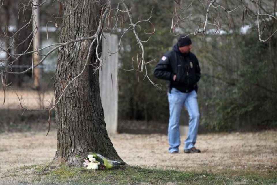 Photo -  Flowers delivered by a mourner lie at the base of a tree as investigators work at the scene of a suspected mass homicide where at least 5 children were slain Tuesday, Feb. 2, 2021 in Muskogee, Okla. [Photo by Mike Simons, Tulsa World]