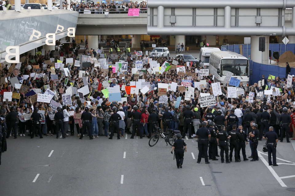 Photo - Police officers block demonstrators from marching  on Sunday on the lower roadway during a protest against President Donald Trump's executive order banning travel from seven Muslim-majority countries, at Los Angeles International Airport. (AP Photo/Ryan Kang)