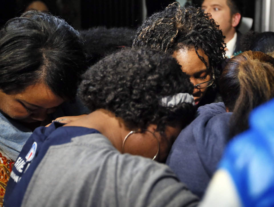 Photo - Supporters of the victims of former Oklahoma City police officer Daniel Holtzclaw pray after the verdicts were read for the charges against him at the Oklahoma County Courthouse in Oklahoma City, Thursday, Dec. 10, 2015. Holtzclaw was found guilty of 18 of the 36 counts. He was accused of sexually assaulting 13 black females between December 2013 and June 2014. Photo by Nate Billings, The Oklahoman