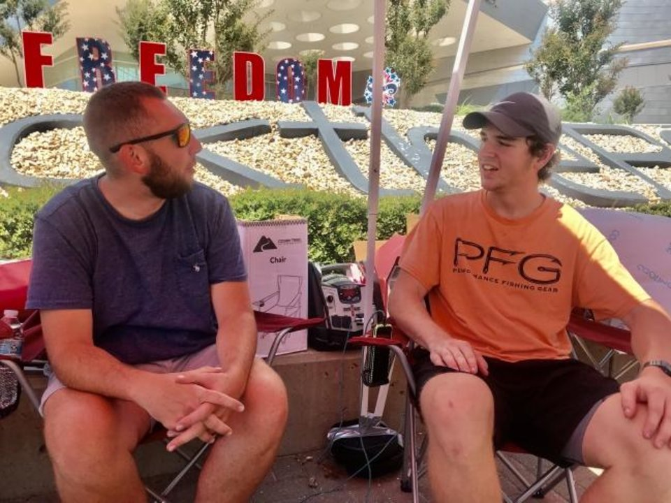 Photo -  Preston Hanning and Stephen Corley, Trump supporters from Broken Arrow, talk on Wednesday under a tent set up outside the BOK Center at 200 S Denver in downtown Tulsa. [Carla Hinton/The Oklahoman]