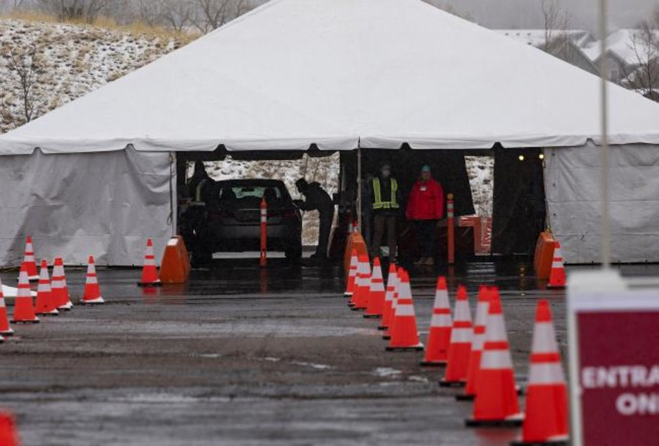 Photo -  Health workers test people at the drive-through coronavirus testing site that opened on Friday by UCHealth in Colorado Springs, Colo. Drive-through testing is not available yet in Oklahoma. [Chancey Bush/The Gazette via AP]