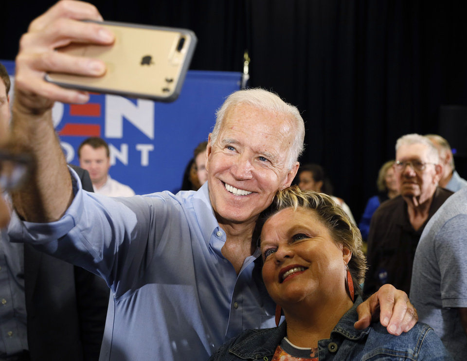 Photo -  Democratic presidential candidate and former Vice President Joe Biden poses for a photo with an audience member after speaking at Clinton Community College, Wednesday in Clinton, Iowa. [Charlie Neibergall/The Associated Press]
