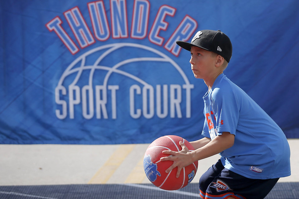 Photo - Jaxton Kitchener, 9, from Salina, Kansas takes aim before shooting a basket outside the arena before an NBA basketball game between the Oklahoma City Thunder and the Sacramento Kings at Chesapeake Energy Arena in Oklahoma City, Sunday, Oct. 21, 2018. Photo by Bryan Terry, The Oklahoman