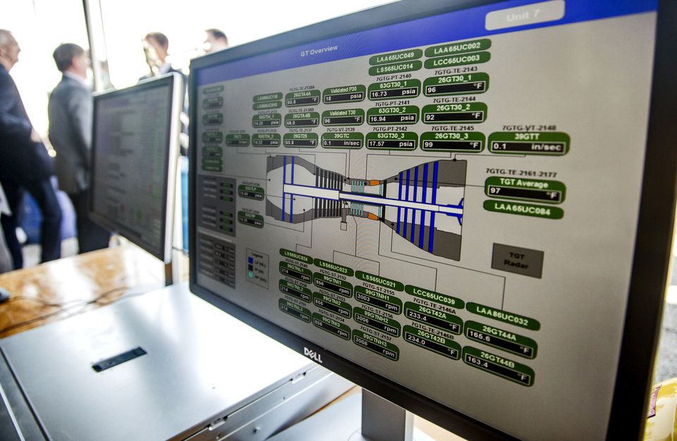 Photo -  Computer monitors show the operation of OG&E's new natural gas-fired power generators during a dedication of the units at the Mustang Energy Center in western Oklahoma City. [Photo by Chris Landsberger, The Oklahoman]