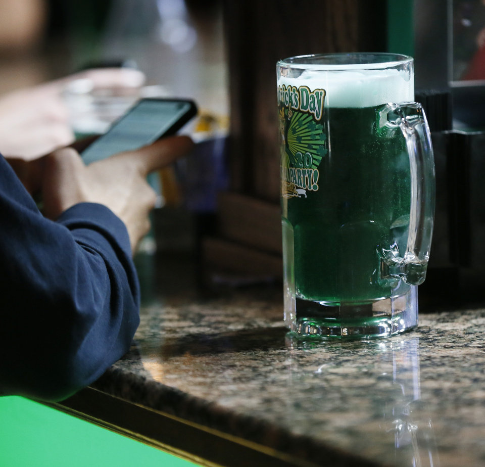 Photo - A green beer sits on the bar next to a customer at O'Connell's Irish Pub and Grille on St. Patricks Day in Norman, Okla., Tuesday, March 17, 2020. O'Connell's was following the restrictions at the time to have no more than 50 people gathered together and limited the number of customers allowed in at once. [Nate Billings/The Oklahoman]