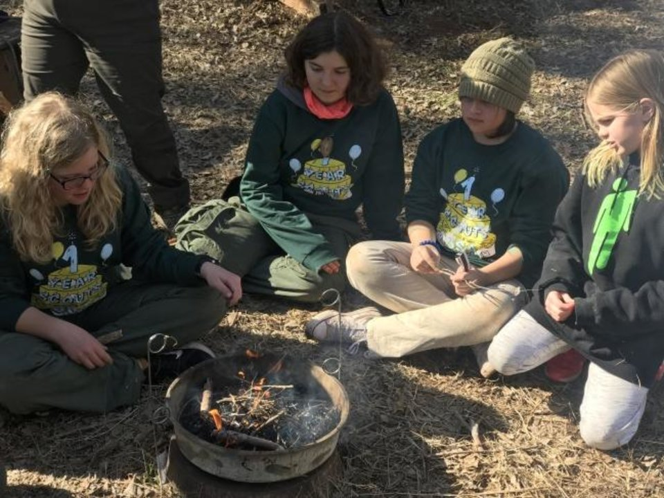 Photo -  Girls participate in a fire-making lesson at a Scouts BSA campout at the John W. Nichols Scouts Ranch in Mustang. They are: Chloe Kessler, Skyler Gee, Faith Randell and Olivia Womack. [Carla Hinton/The Oklahoman]