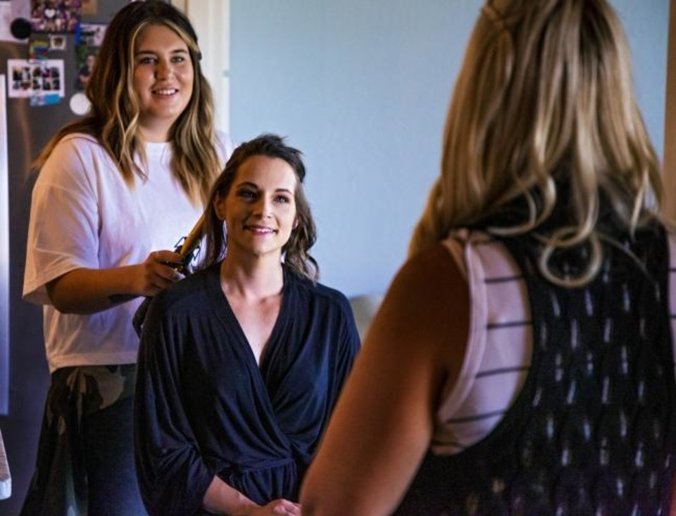 Photo -  Hair and makeup artist Ashlee Medina curls the hair of Southern Belle Boudoir photography client Becky English as they talk to photographer Rachel Birchett at the in-home studio in Oklahoma City on June 2. [Chris Landsberger/The Oklahoman]