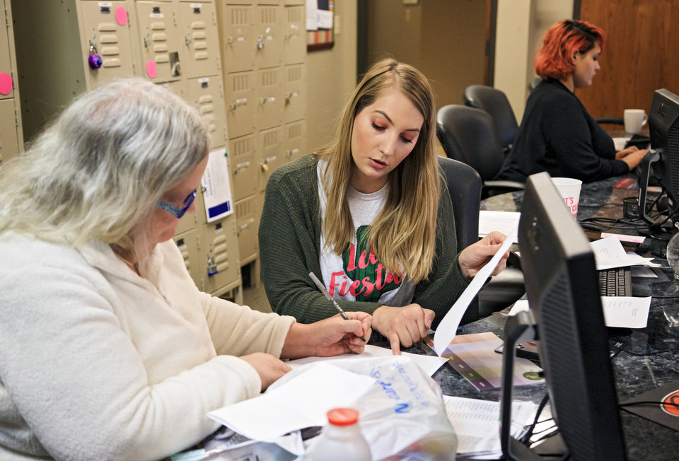 Photo -  Housing coordinator Ashley Burke, right, helps Debbie Ailshire complete paperwork for housing at Thunderbird Clubhouse in Norman on Wednesday. [Photo by Chris Landsberger, The Oklahoman]
