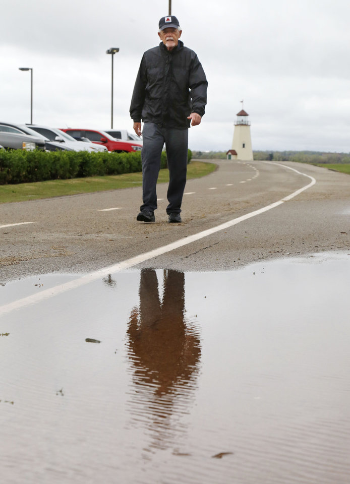 Photo -  Kevin Avery walks past standing water from Tuesday evening's heavy rains while walking the trail at Lake Hefner in Oklahoma City. More rainfall is forecast in the area into next week. [Photo by Paul Hellstern, The Oklahoman]