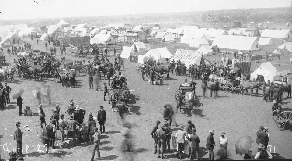 Photo -  In this April 27, 1889, photo provided by the Oklahoma Historical Society, horses and their owners make their way through crowds of settlers who staked claims during the April 22, 1889, Oklahoma Land Run. PHOTO PROVIDED