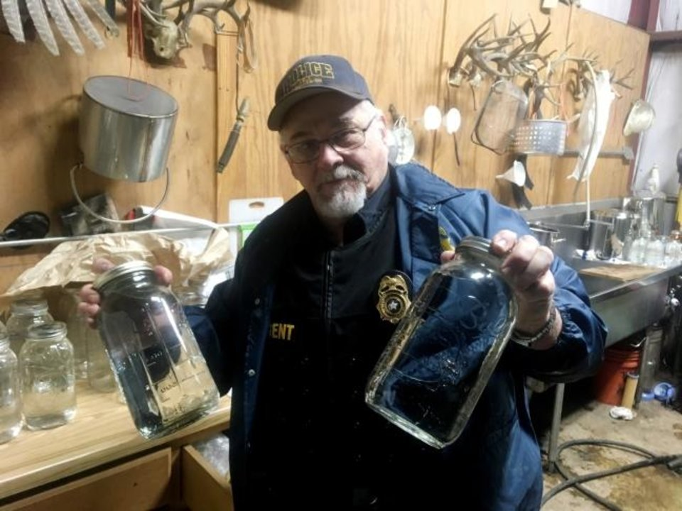 Photo -  Joe D. Daniels, special agent-in-charge of the ABLE Commission's McAlester District Office, shows evidence seized during the raid of a moonshine distillery. [PROVIDED]