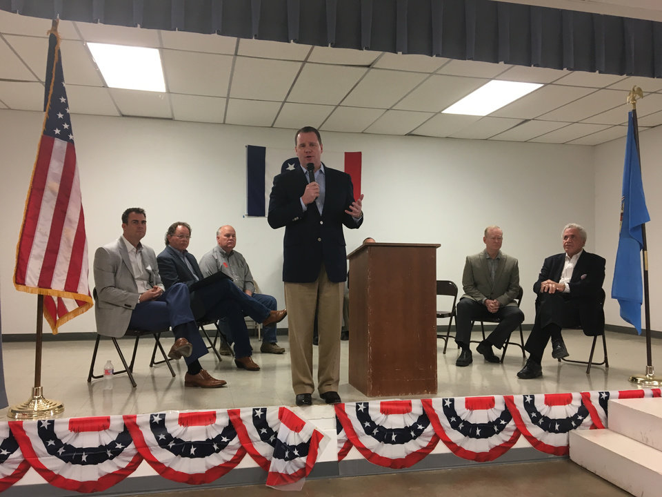 Photo -  Lt. Gov. Todd Lamb speaks Saturday to Logan County Republicans in Guthrie at an event featuring six candidates for the GOP gubernatorial nomination. Seated, from left to right, are Kevin Stitt, Dan Fisher, Gary Jones, Mick Cornett and Gary Richardson. [Photo by Chris Casteel, The Oklahoman]