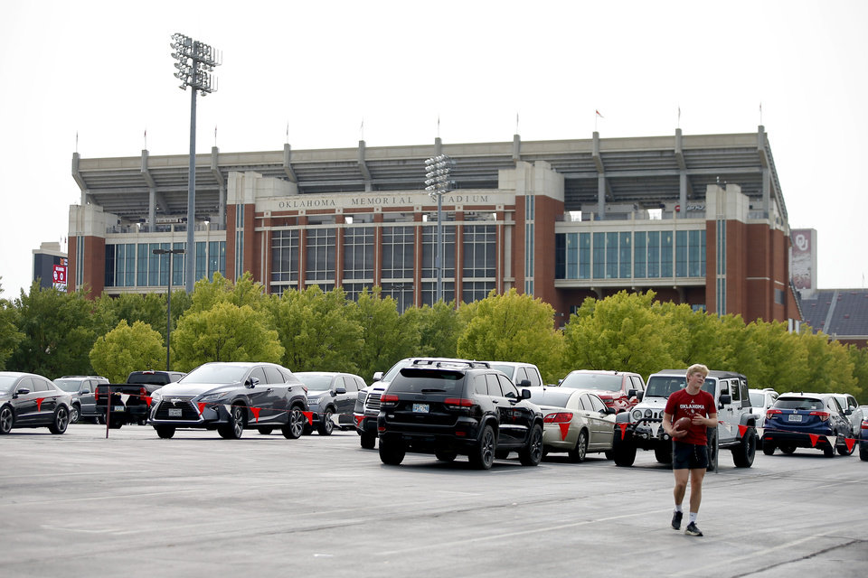 Photo - A fan plays football in a parking outside Gaylord Family-Oklahoma Memorial Stadium a college football game between the University of Oklahoma Sooners (OU) and Missouri State in Norman, Okla., Saturday, Sept. 12, 2020. [Bryan Terry/The Oklahoman]