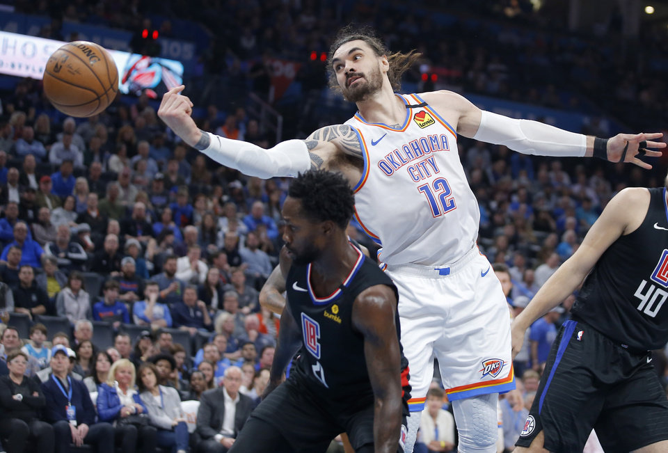 Photo - The ball goes past Oklahoma City's Steven Adams (12) over LA's Patrick Beverley (21) during an NBA basketball game between the Oklahoma City Thunder and the Los Angeles Clippers at Chesapeake Energy Arena in Oklahoma City, Tuesday, March 3, 2020. [Bryan Terry/The Oklahoman]