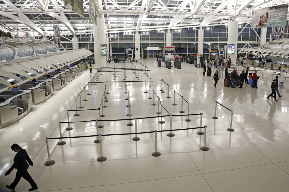 Photo -  People visit an international terminal at John F. Kennedy airport, Friday, March 13, 2020, in New York. A ban on travelers from most European countries begins at midnight Friday, and travelers returning from there will be screened. The ban is the latest calamity for a global travel industry already reeling from falling bookings and canceled reservations as people try to avoid contracting and spreading the coronavirus. (AP Photo/Kathy Willens)