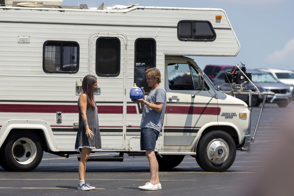 Photo -  Tammin Sursok and Tom Felton stand outside an RV between takes Aug. 3 as they film a scene on the set of Whaling at Frontier City in Oklahoma City. [Photo by Bryan Terry, The Oklahoman]