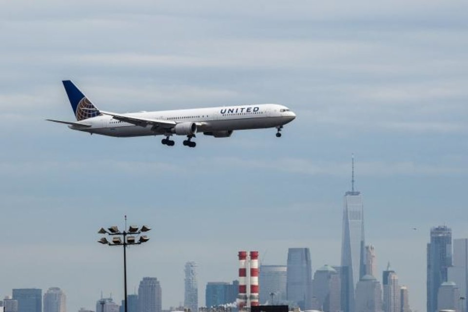 Photo -  In this 2017 file photo, a United Continental airplane prepares for landing as the New York City skyline stands in the background at Newark Liberty International Airport. [Timothy Fadek/Bloomberg]