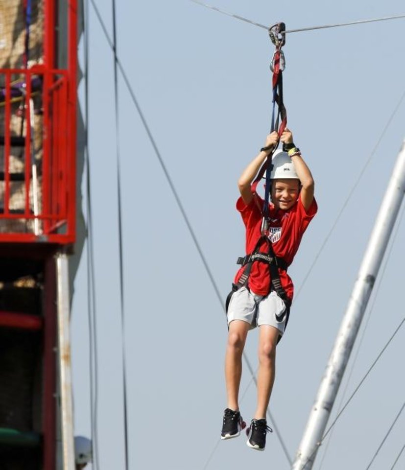 Photo -  Beckett Lawson, 7, rides a zip line during Kanakuk KampOut! day camp. [Nate Billings/The Oklahoman]