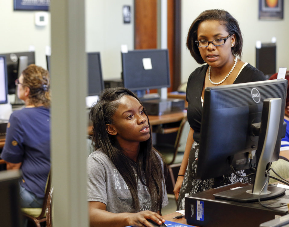 Photo -  Inazereth Geionety, right, helps Shaquez Johnson conduct a job search on a computer at an OK Workforce center in Oklahoma City Monday. The center serves as a resource for a variety of employment needs for Oklahomans. [Photos by Nate Billings, The Oklahoman]