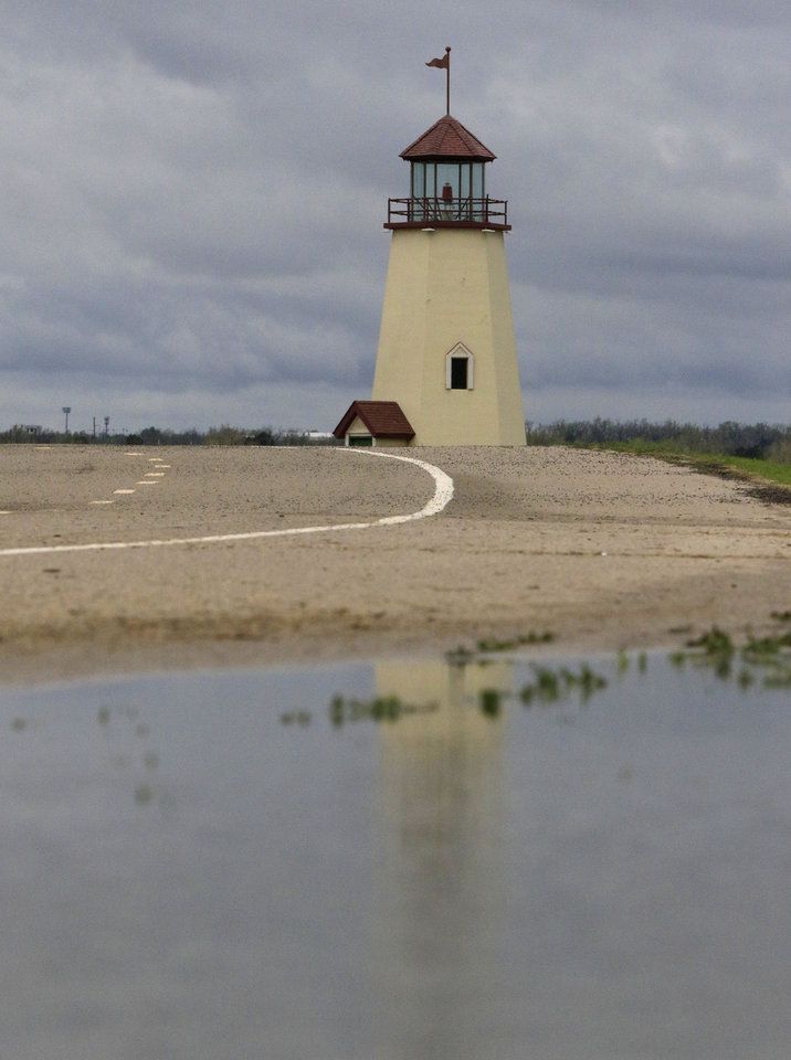 Photo -  Standing water left from Tuesday evening's heavy rain reflects a lighthouse on the eastern bank of Lake Hefner in Oklahoma City. Heavy rainfall Tuesday night and Wednesday morning helped ease drought in the area. [Photo by Paul Hellstern, The Oklahoman]