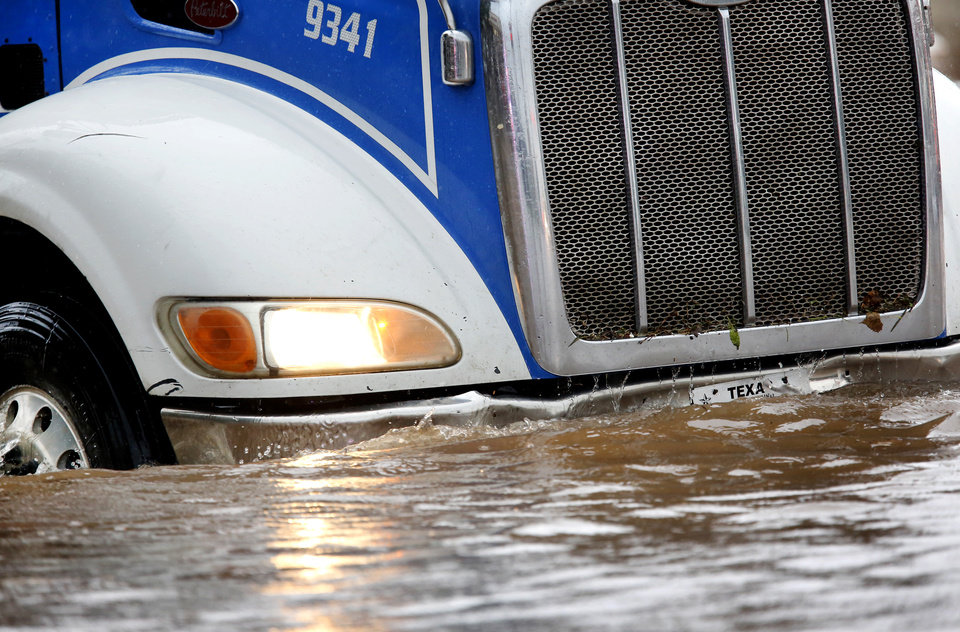 Photo - A big-rig tractor is moving through bumper-deep water on SW 29 Street after heavy rains overwhelmed stormwater drainage systems and  flooded streets, requiring  high water rescues in Oklahoma City as another round of severe storms passes through the metro. The National Weather Service reports up to 1.5 inches of rain fell during a 30-minute period Thursday, June 6, 2019,  in the western part of the Oklahoma City area. This photo taken at  intersection of SW 29 and May.  [Jim Beckel/The Oklahoman]