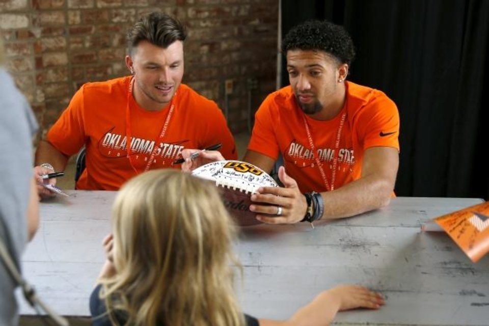 Photo -  Quarterbacks Dru Brown, left, and Spencer Sanders sign a football during Oklahoma State's Fan Appreciation Day inside Gallagher-Iba Arena Saturday. [Bryan Terry/The Oklahoman]