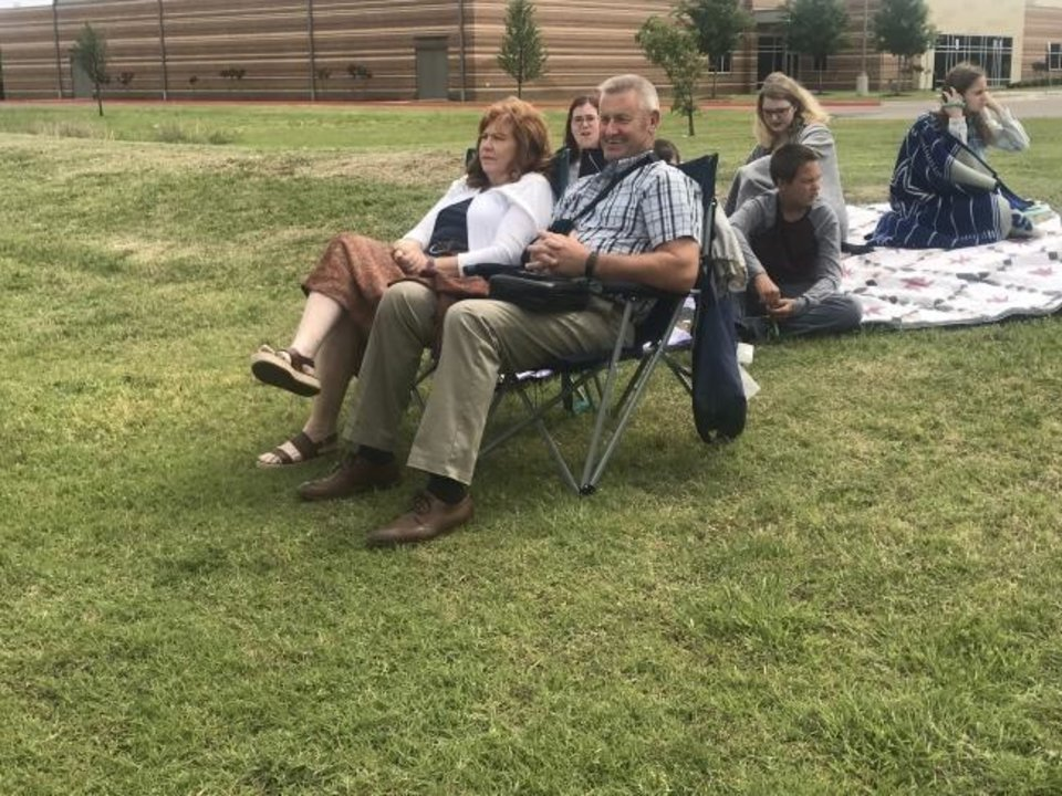 Photo -  Liz and Mickey Colvard sit on lawn chairs next to their children sitting on blankets during